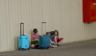 Kids seated next to luggage