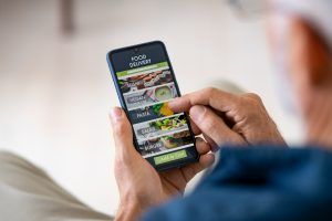 Man using mobile app to order delivery food Variety